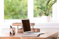 Tabla con el ordenador portátil y efectos de escritorio imagenes de archivo