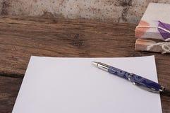 Tabla con el papel y la pluma Foto de archivo libre de regalías