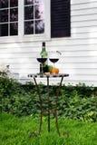 Tabla con la botella de vino y de vidrios en jardín cerca de la casa Foto de archivo libre de regalías