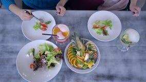 Tabla con la comida y los vidrios sanos jugo, manos de comer a gente con las bifurcaciones cerca de las placas almacen de video