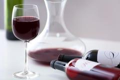 Tabla con la copa y las botellas de vino rojo Fotos de archivo