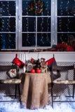 Tabla con la decoración de la Navidad, medias, guirnalda de la Navidad, vela roja, linterna Imágenes de archivo libres de regalías
