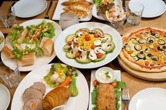 Tabla con la diversa comida servida. Fotos de archivo libres de regalías