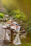 Tabla con la invitación festiva y mantel en el jardín del verano fotografía de archivo