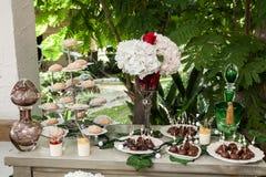 Tabla con la torta, los dulces y los postres para la recepci?n de bodas y los partidos imagenes de archivo