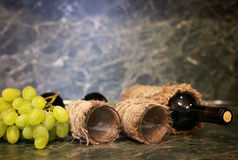 Tabla con la uva de la botella de vino Imagen de archivo