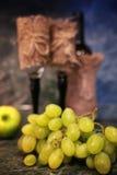 Tabla con la uva de la botella de vino Fotos de archivo libres de regalías