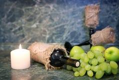 Tabla con la uva de la botella de vino Imágenes de archivo libres de regalías