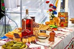 Tabla con las bebidas y la comida Imagenes de archivo