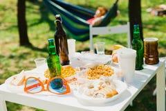 Tabla con las botellas de cerveza y de comida en la fiesta de jard?n del verano imagenes de archivo