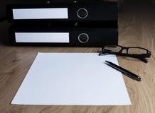 Tabla con las carpetas, hoja blanca vacía, vidrios, pluma fotos de archivo libres de regalías