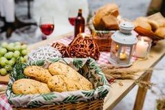 Tabla con las cestas de galletas y de pan, vino, velas fotos de archivo