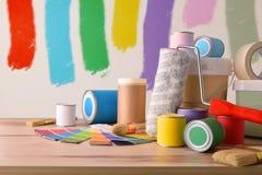 Tabla con las herramientas de la pintura para el fondo pintado casero de la pared imagen de archivo