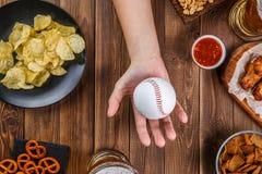 Tabla con las manos con béisbol Imagenes de archivo