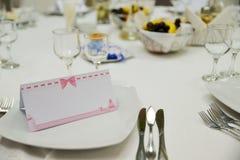 Tabla con las placas, los cubiertos y la tarjeta de felicitación Foto de archivo