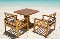 Tabla con las sillas en la playa tropical en Maldivas Imagen de archivo libre de regalías