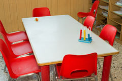 Tabla con las sillas rojas de una clase de escuela para los niños Foto de archivo libre de regalías