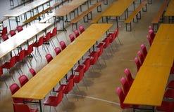Tabla con las sillas rojas en un cuarto ancho del almuerzo foto de archivo