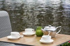 Tabla con las tazas y la tetera blancas en la calle cerca del agua Fotografía de archivo libre de regalías