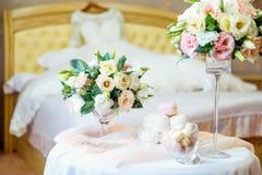 Tabla con los detalles del ` s de la novia: ramo de flores del eustoma, joyería, perfumes y melcocha y dulces de los macarrones c Imagen de archivo libre de regalías