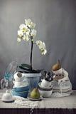 Tabla con los platos y la orquídea blanca Fotografía de archivo libre de regalías
