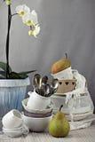 Tabla con los platos y la orquídea blanca Fotos de archivo