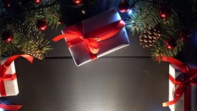 Tabla con los regalos y el árbol de navidad del Año Nuevo con las luces borrosas del centelleo almacen de video