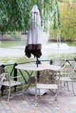 Tabla con un paraguas en el lago Fotos de archivo