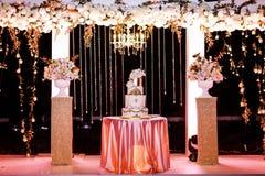 Tabla con un pastel de bodas, las velas, la luz y las flores Decoración de la boda foto de archivo libre de regalías
