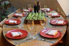 Tabla cubierta con las manzanas y el vino en el centro de la tabla Fotos de archivo