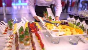 Tabla de banquete de abastecimiento maravillosamente adornada con canape del bocado en el restaurante o el hotel, camarero de aba almacen de metraje de vídeo