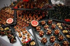 Tabla de banquete de abastecimiento maravillosamente adornada con canape, verduras y frutas fotos de archivo