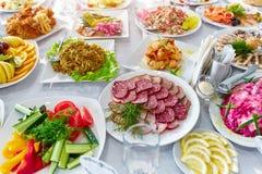 Tabla de banquete de abastecimiento maravillosamente adornada con diversa comida Foto de archivo libre de regalías