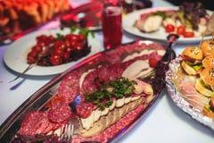 Tabla de banquete de abastecimiento maravillosamente adornada con diversos bocadillos de las hamburguesas de las hamburguesas en  Foto de archivo libre de regalías