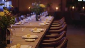 Tabla de banquete completamente determinada grande en un restaurante para la compañía de mucha gente en restaurante moderno por l almacen de metraje de vídeo
