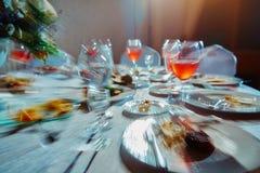 Tabla de banquete con la comida, como él ve a un hombre borracho, un alcohólico que bebió muchas bebidas alcohólicas fotografía de archivo libre de regalías