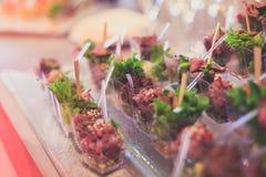 Tabla de banquete de abastecimiento maravillosamente adornada con diversos bocados y aperitivos de la comida Foto de archivo