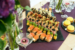 Tabla de banquete de abastecimiento maravillosamente adornada con diversos canapes y aperitivos Imagenes de archivo