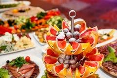 Tabla de banquete de abastecimiento maravillosamente adornada con las frutas frescas en fiesta de cumpleaños corporativa Foto de archivo
