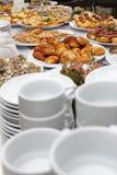Tabla de banquete del abastecimiento con bocados, bocadillos, tortas, tazas y placas cocidos de la comida Fotos de archivo
