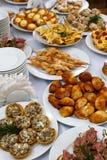 Tabla de banquete del abastecimiento con bocados, bocadillos, tortas, tazas y placas cocidos de la comida Imagen de archivo libre de regalías