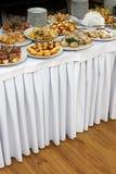 Tabla de banquete del abastecimiento con bocados, bocadillos, tortas, tazas y placas cocidos de la comida Foto de archivo libre de regalías