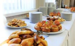 Tabla de banquete del abastecimiento con bocados, bocadillos, tortas y placas cocidos de la comida Imagen de archivo