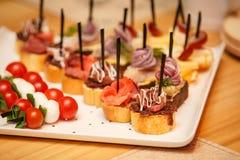 Tabla de banquete del abastecimiento con diversos bocados de la comida Imagenes de archivo