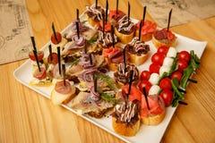 Tabla de banquete del abastecimiento con diversos bocados de la comida Foto de archivo