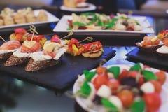 Tabla de banquete del abastecimiento con diversos bocados y aperitivos de la comida en evento corporativo de la fiesta de cumplea Fotos de archivo