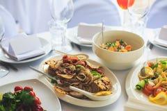 Tabla de banquete del abastecimiento con diversos bocados y aperitivos de la comida en evento corporativo de la fiesta de cumplea Foto de archivo