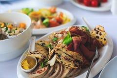 Tabla de banquete del abastecimiento con diversos bocados y aperitivos de la comida en evento corporativo de la fiesta de cumplea Imagenes de archivo