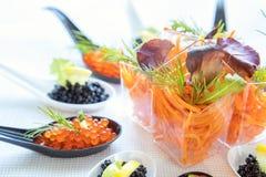 Tabla de banquete del abastecimiento con la ensalada y el caviar Imagen de archivo