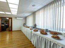 Tabla de banquete del abastecimiento en pasillo al lado de la sala de conferencias Imágenes de archivo libres de regalías
